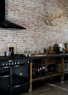Industrial kitchen with modern appliances. Exposed brick and timber
