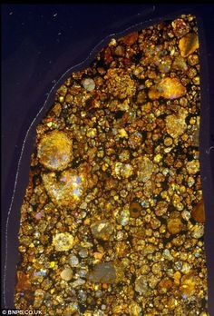 Macro enlargement of a piece of meteorite. Photographs of the colourful interiors of meteorites. The space rocks are usually known for their dull exterior, but scientist Jeff Barton has shown the dazzling world beneath the grey surface. He has photographed hundreds of 4.5 billion-year-old meteorites by using a standard SLR camera and a powerful microscope to zoom in on fragments of the rocks.