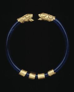 Lion Head Bracelet late 6th Century BC Etruscan The blue glass hoop of the bracelet terminates at each end with a lion head made of sheet gold. Behind the base of each lion head is a collar decorated with two spirals and a palmette in filigree. The four loosely fitted gold bands on the hoop slide back and forth. This is a very rare piece; one other complete example that has survived is a bracelet found in a tomb in Monte Autò, now in the Museo di Villa Giulia in Rome. Fragments of glass…