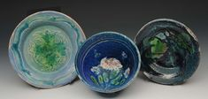 """Quentin Bell (British, 1910-1996) A Fulham Pottery blue bowl painted with flowers, inscribed signature and pottery, 5 3/4"""" diameter and two further Quentin Bell Fulham Pottery dishes, each signed, 7"""" diameter and 6"""" diameter (3)."""