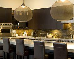 Very modern dark lighting over kitchen island.