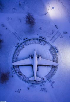 Best Aerial Drone photography from around the world - WWII airplane by Salim Madjd A World War 2 airplane at the outdoor display of the Belarusian Great Patriotic War Museum is caked in snow from a light snowstorm overnight, with a photo taken during 'blue hour' in the early morning.   Skypixel Drone Photo Competition  Drone Magazine Australia News