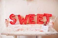 Lighted marquee letters create a whimsical dessert table backdrop. #Whimsical #Wedding