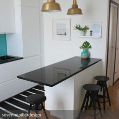 Schlichter Küchentresen mit Barhockern - insbesondere geeignet für offene Küchen mit wenig Platz. Schick: die goldenen Industrie-Leuchten über dem Tresen
