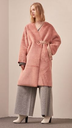 The Valenxina Shearling Coat in pink. Super soft, clean, collarless with V-neckline silhouette and outlined with brick suede. Dropped shoulder, wrap front with button closing. Loose silhouette. COMPOS