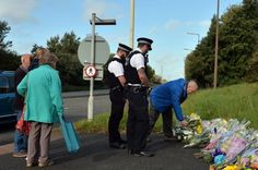 Police officers lay flowers near to the scene in Wallasey, northwest England