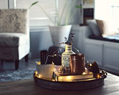 coffee table decor - galvanized metal tray with remote, bronze candle, vase with eucalyptus and fairy lights