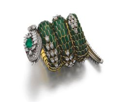 Emerald, enamel and diamond bracelet-watch, 'Dragon', Bulgari, 1960s Articulated body composed of green enameled scale-like links, highlighted with marquise-shaped diamonds, head and tail pavé-set with brilliant-cut, marquise- and pear-shaped diamonds, eyes accented with cabochon rubies, head further embellished with a pear-shaped emerald and opening to reveal a circular watch, the dial signed Jaeger-LeCoultre, the bezel set with single-cut diamonds, signed Bulgari, box signed Bulgari.
