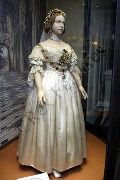 1840 Wedding dress worn by Queen Victoria. White satin gown trimmed with a deep flounce and trimmings of hand-made lace. Orange flower blossoms, also trimmed the dress and made up Victoria's wreath, which she wore instead of a tiara. The veil was 4 yards in length. Her jewellery consisted of diamond earrings and necklace, and a sapphire brooch. The train measured 5.5m long. Although she wasn't the first royal bride wearing white, the colour became quickly popular with Victorian era elites.