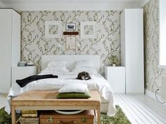 Green floral wallpapered bedroom with tall wardrobes on each side of the bed.