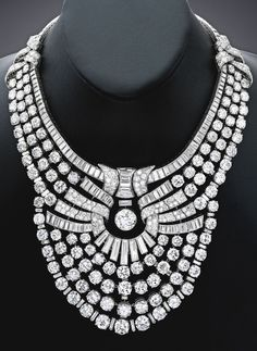 Magnificent and Historic Platinum and Diamond Necklace, Van Cleef & Arpels, France. The graduated line necklace supporting a flexible bib in the form of a sunburst, centred by an articulated round diamond weighing approximately 6.00 carats, set with 118 larger round diamonds, accented by smaller round diamonds, completed by baguette diamonds, with French assay and maker's marks; 1939. #VanCleef #Arpels #ArtDeco #necklace