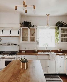 White kitchen with butcher block countertops and retro-inspired light fixtures