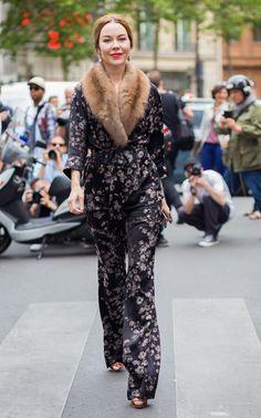 Ulyana Sergeenko é fotografada andando pela rua usando conjunto de pijamas preto com estampa floral e gola de pele