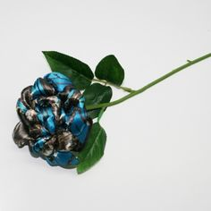 """This long stem blue camo rose is perfect for your camo wedding, country wedding. It is about 4 - 4 1/2"""" across, and mounted on a 13"""" rose stem, along with 5 green leaves."""