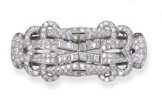 AN ART DECO DIAMOND DOUBLE-CLIP BROOCH  Each clip designed with openwork pavé-set diamond scalloped terminals to the baguette-cut V-shaped twin-line centre, circa 1930, 6.3 cm. wide