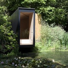 The Forest Pond House is a wooden folly that cantilevers across a garden lake in Hampshire, England, by TDO.