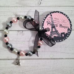 Paris Eiffel Tower charm bracelet. It is a 6 1/4 inch bracelet on stretchy cord with round grey, silver and pink acrylic pearl like beads and