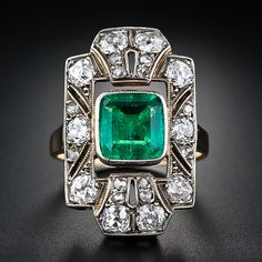 A bright and glistening green emerald, weighing 1.50 carats, is the center of attention of this big and beautiful early twentieth century antique dinner ring - crafted in platinum over 18 karat gold. The bezel-set emerald floats inside a geometric buckle motif frame sparkling with 1.50 carats of old mine-cut and rose-cut diamonds. This fun, festive and impressive bauble measures a tad over one-inch long by 5/8 inch wide.