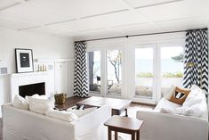 Smitten Studio - cabin living room redo - white walls, black print with white mat and black frame above white fireplace, black and white chevron crapes, white upholstery, wood with black railroad cart (lovely!), cream area rug, black and white cowhide under railroad lights, brass arm flor lamps, dark wood floors
