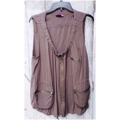 """High-low tan vest top High on the back low in the front tan vest top. 3 decorative zip pockets on the front and long zipper. Deep scoop neck. 100% rayon. Size 2X. Measurements: bust 50"""", front length 26"""", back length 17 1/2"""". Tops Tank Tops"""