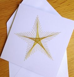 Christmas/ Holiday Card String art inspired design on card. The image is created by embroidering gold thread to form a Christmas star. White card with blank white paper insert. Two sizes available: 10 cm (4 inches) square - £2.25 13.5 cm (5.3 inches) square - £2.75 Or how about a