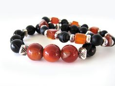 Gorgeous beaded stretch bracelets featuring 12mm red banded agate beads, 10mm black buri seed beads (made from the seeds of a Buri palm tree in Indonesia), amber horn diced beads, 8mm matte black agate beads and pewter accent beads. Bracelet can be worn as shown or individually for a more simple statement. A definite must-have bracelet for those spring/summer outfits that will transition well when moving into cooler weather clothing.