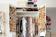 Hvit garderobe med åpne dører, fylt med klær