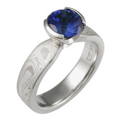 Blue Sapphire Mokume Solitaire Tapered Engagement Ring - This simple yet enchanting ring has a classic design with a contemporary twist. The band has a uniform width until it intersects the head with an elegant taper. The setting tapers down to the band allowing for the unique engagement ring to sit flush next to a flat wedding band. - This White mokume gane engagement ring is set with a round blue sapphire in a semi-bezel.