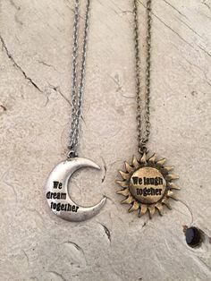 moon necklace Two friendship necklaces in silver and gold feature engraved charms of a sun and moon. The silver moon necklace reads - We dream together. The