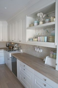 Wood countertops, white cabinets.
