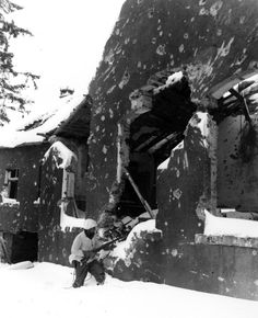 Pfc. D. C. Cox searches a ruined building in Mürringen, Belgium for German snipers (January 30, 1945)