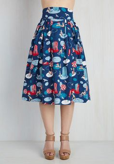 Looking for more retro options in your closet? Then it's time to rock the groovy, beach-themed print of this navy cotton skirt! From hard-to-find British brand Emily and Fin, this pleated midi is home to an array of red and teal sunbathers, offering a look that's undeniably swell.