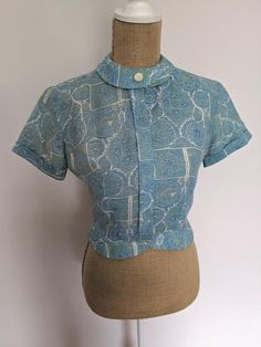 This blouse is so gorgeous! Lightweight cotton with mostly blue and hints of green in mandela pattern. Has overlapped collar with large pearlescent button. Has concealed front button closure with cropped length and peplum waist. Short sleeved with folded cuffs. In excellent vintage condition, has Mandela Patterns, Sarong Dress, 1950s Outfits, Mandala Print, Summer Blouses, Embroidered Blouse, Front Button, Beautiful Dresses, Cuffs