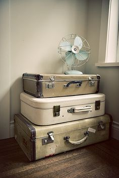 a corner filled with stacked suitcases and a pretty blue fan. i image pretty vintage blankets and some inspirational magazines being stored inside the suitcases.