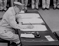 Gen. Douglas MacArthur signs as Supreme Allied Commander during formal surrender ceremonies on the USS MISSOURI in Tokyo Bay. September 2, 1945.