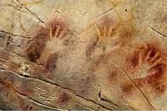 This undated photo shows a detail of the 'Panel of Hands' in El Castillo Cave, Spain, showing red disks and hand stencils made by blowing or spitting paint onto the wall. A date from a disk shows the painting to be older than 40,800 years, making it the oldest known cave art in Europe.    Pedro Saura/AAAS/AP