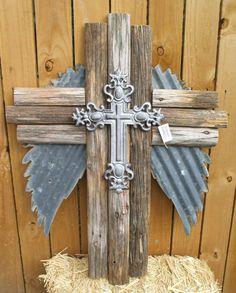 Triple wooden Cross, with cast Iron Cross, and corrugated metal angel wings. Size is aprox. 34 tall and 25 wide. Made from reclaimed fence