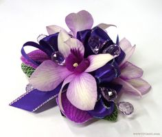 Custom Daddy Daughter Dance corsage wristlet of lavender dendrobium orchid blooms with iridescent-edge purple satin ribbon and sprays of faceted acrylic teardrops in lilac | Flowers by Viviano Flower Shop