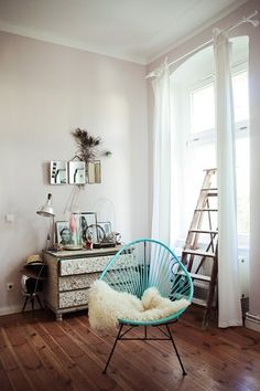 Gorgeous blue wire chair with a fluffy rug on it! I love it! It looks so sparse but homely at the same time