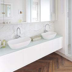 White modern bathroom with wall-hung vanity unit and wood flooring