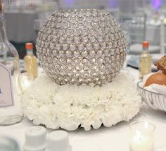 White carnations with a crystal globe candle holder.