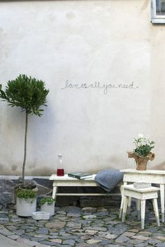 Lovely courtyard.... vintage white bench and table, bottles, nice use of greens, and cute quote...x