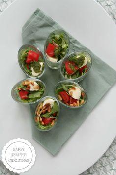 Het eerste recept uit het kerstmenu: amuse rucola salade met mozzarella en cherrytomaatjes in een glaasje. www.lekkeretenmetlinda.nl