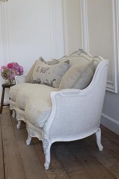 pale grey and white french sofa, with matching cushions, and white armrests and legs, on rough vintage wooden floor, near stool with flower vase French Sofa, French Chairs, Shabby Chic Armchair, Antique Couch, Wooden Table And Chairs, Beige Sofa, Country House Interior, Stylish Beds, Shabby Chic Bedrooms