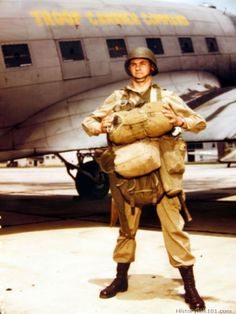 A GI in full parachute dress stands in front of the Troop Carrier Command. Airborne Infantry Training Center