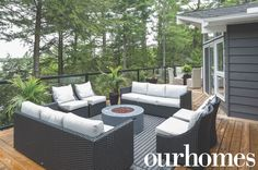 A big outdoor seating area, with a fireplace table, surrounded by tall trees at a cottage.