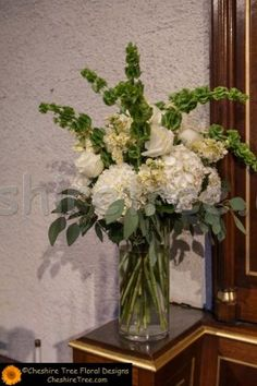 Tall arrangements in clear glass vases created using white hydrangea, white roses, cream matthiola, bells of Ireland and eucalyptus.