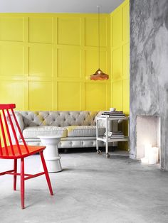 Oslo-based Inne Design have kept simplicity while bringing a bright contrast with the red wooden chair and canary yellow panelling behind, while bringing the scheme together with the grey comfy sofa and grey cement wall.