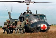 """A wounded member of the 1st Plt. Company """"C,"""" 25th Infantry Division, is helped to a waiting UH-1D """"Iroquois"""" helicopter in Vietnam, May 10, 1967, during the Vietnam War. (AP Photo)"""