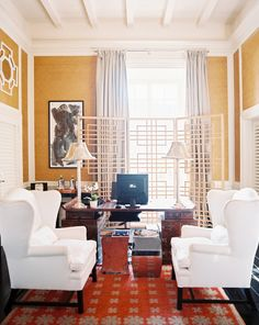 Yellow & red eclectic office design with white wingback chairs, mirrored stools, antique desk, ...